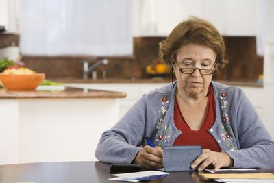 Woman writing a check in her kitchen