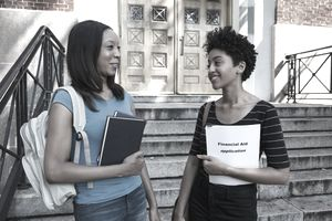Two women stand outside of a college admissions building with one holding a financial aid application
