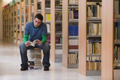 Student sitting on stack of books in library, reading