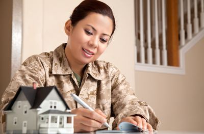 Woman in army fatigues signing check with miniature house in foreground