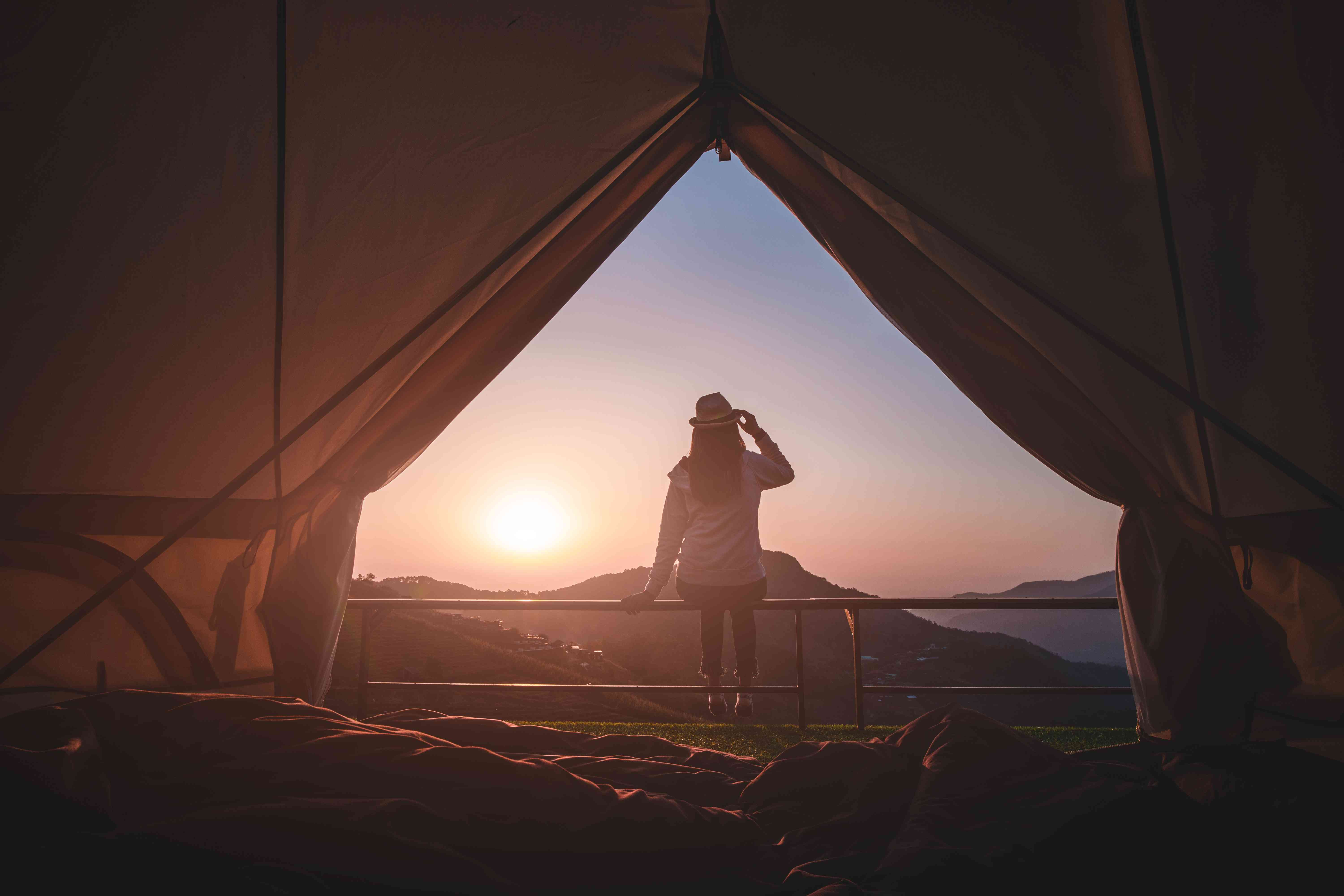 Woman traveler sitting outside camping tent looking at sunrise