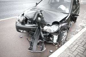 A Car Damaged after a Car Accident sitting by the curb.