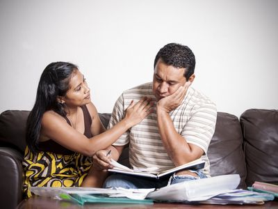 Distressed couple reviews their finances on the sofa with paperwork