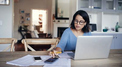 Woman sitting in front of laptop using a calculator to pay her bills online