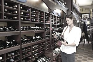 Woman Studying Two Wine Bottles in Wine Shop