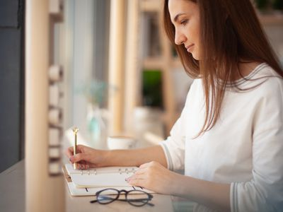Young woman writing in an appointment book, glasses on desk