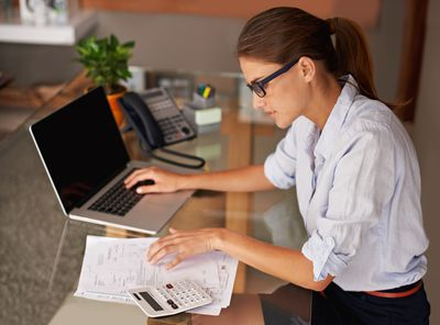 A woman preparing tax return sitting at a desk with a laptop and calculator.