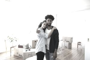 A young couple takes a break from unpacking in their new home they saved a down payment for
