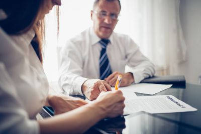 woman signing contract with businessman