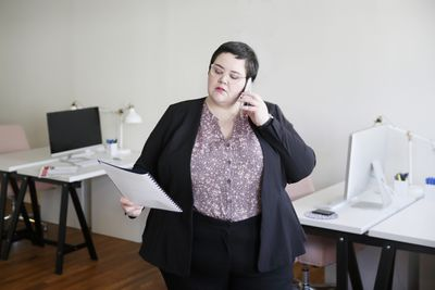 A pA person holds a phone to their ear while reviewing insurance policy documents