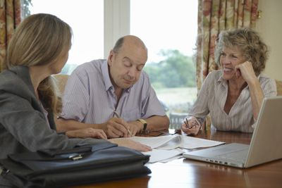 Older couple signs paperwork with an advisor