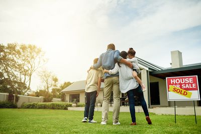 Family in front of a house they just bought