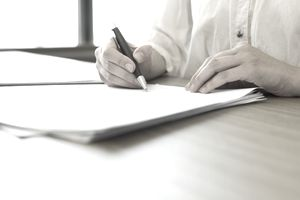 Closeup of man writing on a tax form with pen