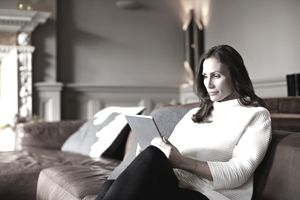 Woman in white turtleneck sitting on couch using digital tablet