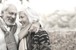 Older couple hugging and smiling in the autumn leaves