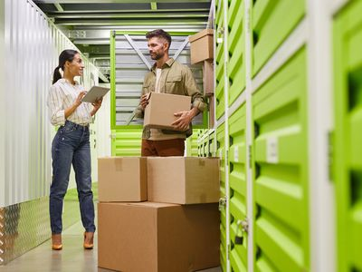 Couple moves boxes into neon green storage unit
