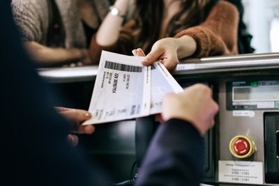 Travellers getting their boarding passes at airline check-in counter.