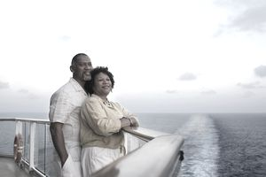 Couple on deck with cruise ship wake behind them