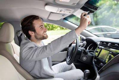 A man in the driver's seat adjusts the rearview mirror