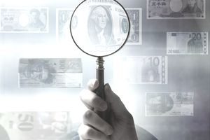 a magnifying glass enlarging a dollar bill among various currency