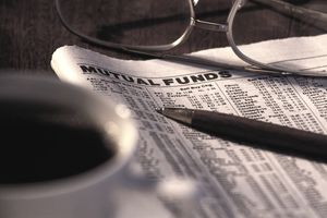 Newspaper turned to the Mutual Funds Section, with glasses, pen, and a cup of coffee