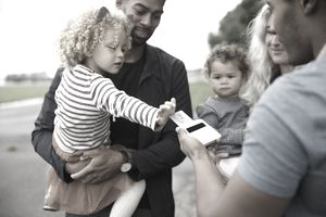 A family makes a purchase with a rewards credit card, while a little girl helps with the transaction