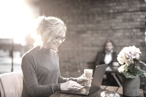Young woman working on laptop outdoors