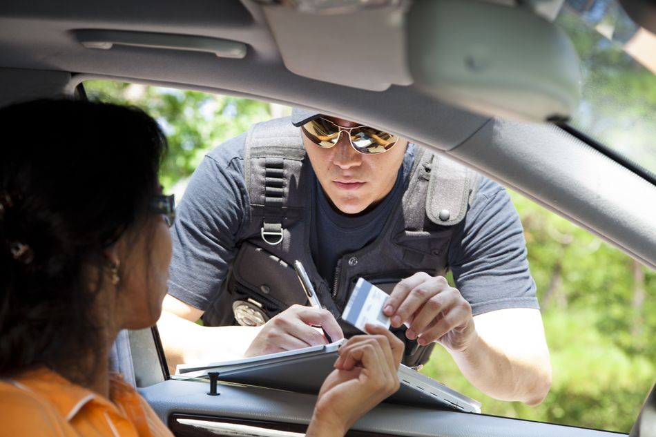 Policeman gives driver a traffic ticket.