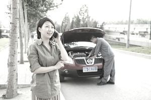 Woman talking on phone while mechanic fixes car