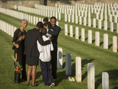 Multigenerational family dressed in black hugs at military cemetery