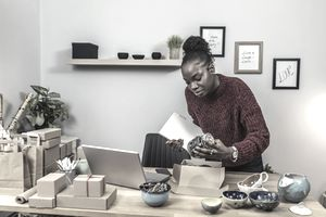 person making pottery and packaging it to sell