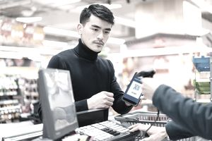 Customer using contactless payment in grocery store