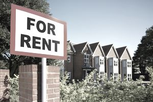 """A """"For Rent"""" in front of a row of rental properties"""