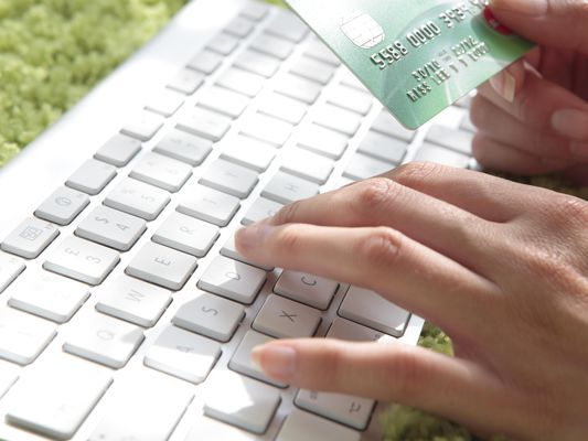 Internet shopping with a person typing on a keyboard with one hand and holding a credit card in the other
