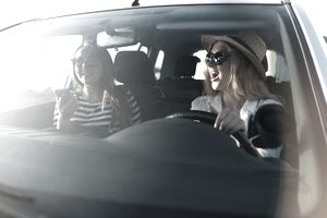 Two smiling young women wearing sunglasses in car