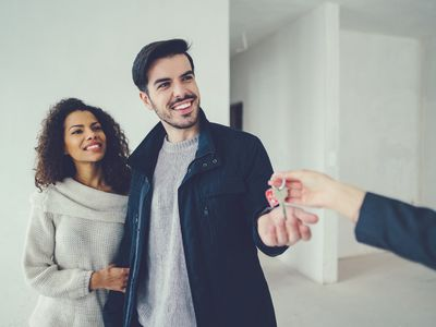 a person hands house keys to a man and woman
