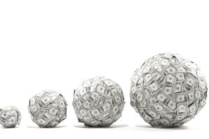 A series of balls composed of dollar bills, increasing in size