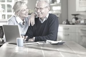 Couple with computer and calculator calculating retirement to live on