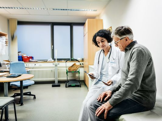 Doctor in a white lab coat talks to an elderly patient about test results.
