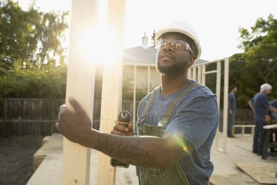 A man working on a construction site wields a drill driver as the sun rises behind him.