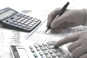 Person with a calculator and pen making notes on a financial analysis spreadsheet.