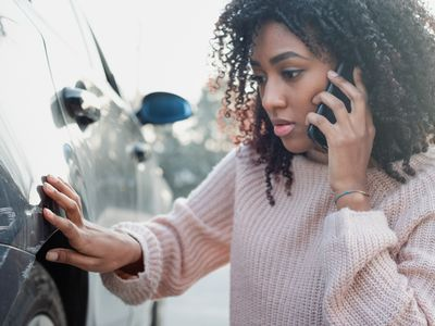 Woman inspecting damage on her car's rear fender and calling her insurance company