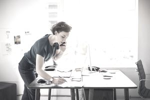 Businesswoman taking notes on phone in bright office