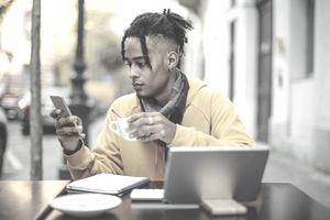 Person in yellow hoodie holds coffee in one hand and a smart phone in other, with notebook and tablet