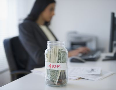 Jar labeled 401k filled with money and a woman working in the background