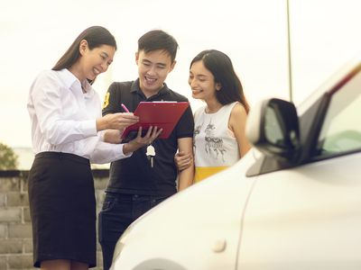 Happy Asian Couple purchasing and signing sales contract for car at dealership