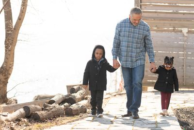 Person walking and holding the hands of two children outside