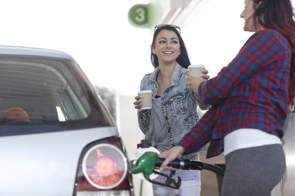Two women smile while at the gas pump; one hands a takeout cup of coffee to the other as she pumps gas into a car.