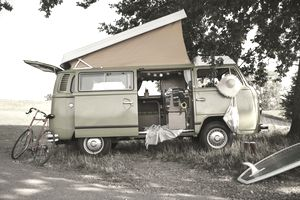 An old campervan with a pop-up tent sits in the shade of a tree with a bike, surfboard, and other gear around it