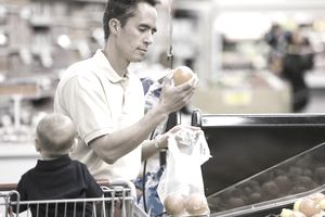 man grocery shopping with baby